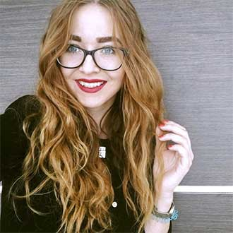 remington instagram red headed woman with glasses smiling at camera