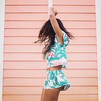 remington instagram woman in tropical outfit jumping sideways