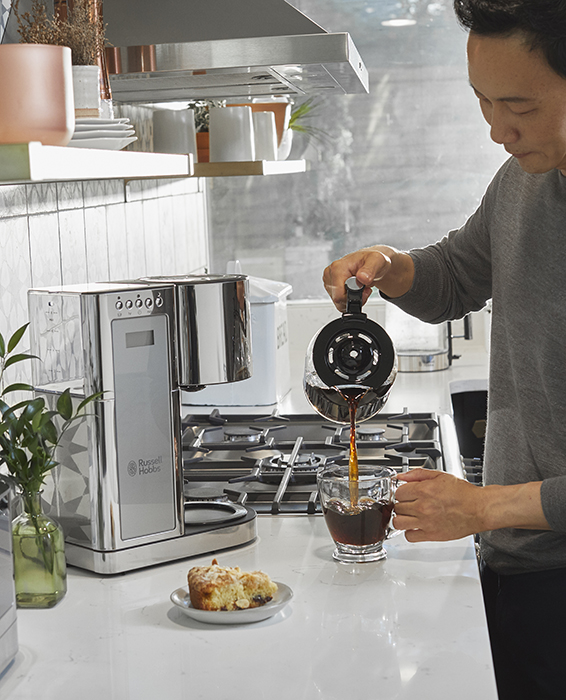 Man pouring coffee using grey glass coffeemaker