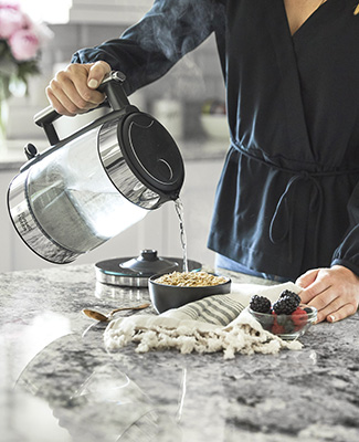 woman pouring hot water onto oatmeal using black glass kettle
