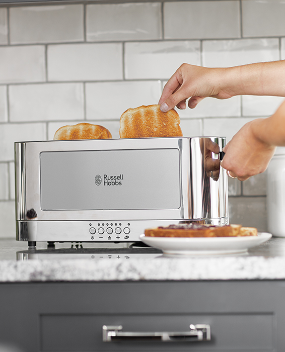 woman pulling toast out of grey glass toaster