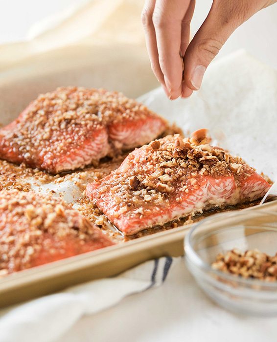 Woman sprinkling chopped pecans | Pecan Crusted Salmon with Coffee Bacon Sauce Recipe | Russell Hobbs